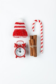 Christmas composition with candy cane, small analog clock, striped hat and cinnamon sticks