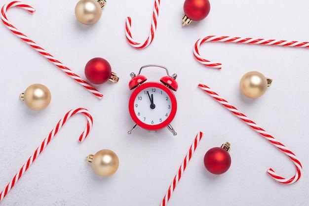 흰색 바탕에 사탕 지팡이, 빨간색 알람 시계, 크리스마스 공이 있는 크리스마스 구성. 새 해 개념입니다. 평면도 - 이미지