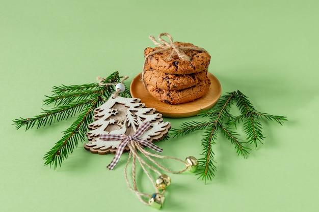 モミの木の枝と木のおもちゃと緑の紙にチョコレートチップクッキーとクリスマスの構成。お祝いのグリーティングカード。