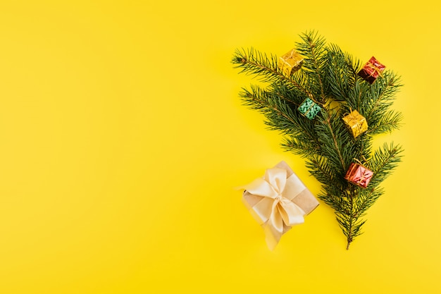 Christmas composition with conifer evergreen tree branches and gift box on yellow
