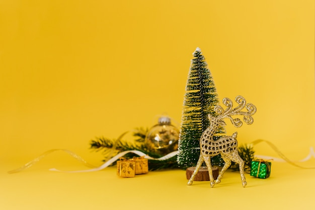 Christmas composition with conifer evergreen tree branches, golden deer and christmas toys on yellow
