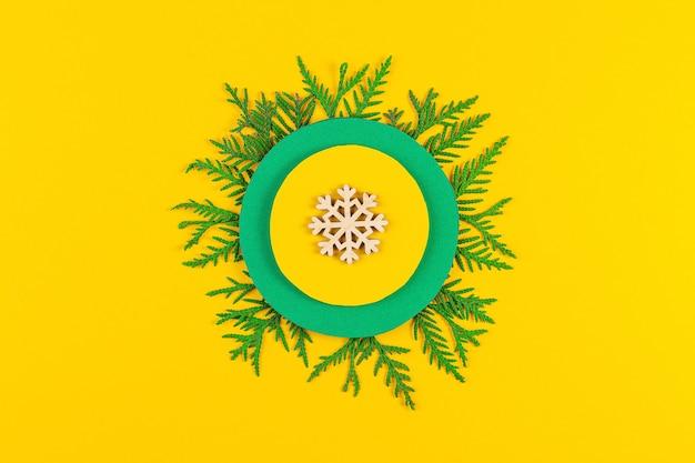 Новогодняя композиция с ветвями хвойных деревьев на фоне желтой бумаги. круглая рамка из ветвей и украшений елки с пространством для текста. вид сверху. новогодняя концепция
