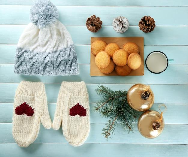 파란색 테이블에 쿠키, 장갑, 장식이 있는 크리스마스 구성
