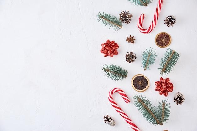 コピースペース付きのクリスマス作曲。白い背景にモミの木の枝、松ぼっくり、お菓子で作られた装飾