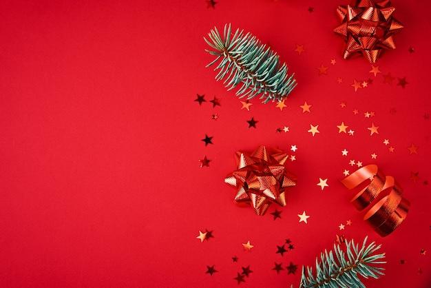 コピースペース付きのクリスマス作曲。赤い背景にクリスマスの装飾とお祝いの紙吹雪とモミの木の枝