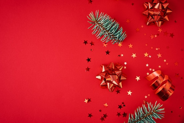 Christmas composition with copy space. fir tree branches with xmas decoration and festive confetti on red background