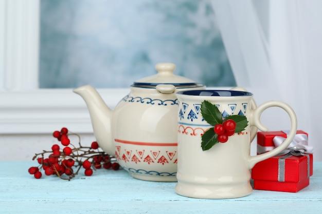 나무 테이블에 컵과 뜨거운 음료 찻주전자가 있는 크리스마스 구성