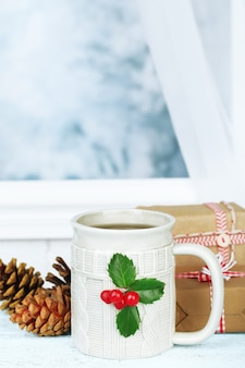 Рождественская композиция с чашкой напитка на деревянном столе