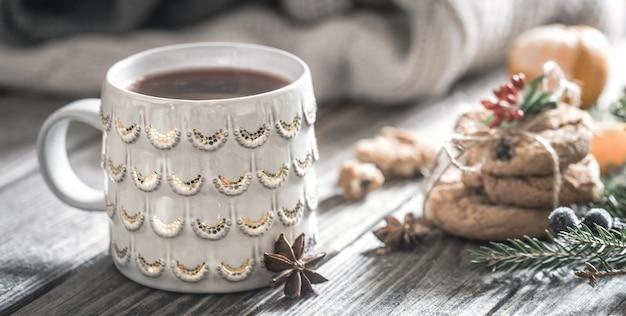 Новогодняя композиция с чашкой чая и печеньем на деревянном фоне, концепция праздника и веселья, фон