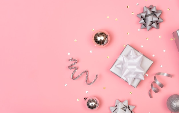 Christmas composition with decorations and gift box with star confetti on pink pastel . winter,  . flat lay, top view, copyspace.