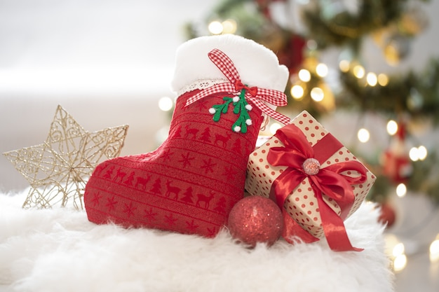Christmas composition with a decorative sock and gift box in a cozy home atmosphere