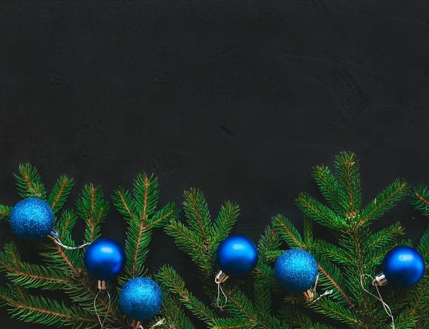 Новогодняя композиция с еловой веткой и синими и золотыми шарами
