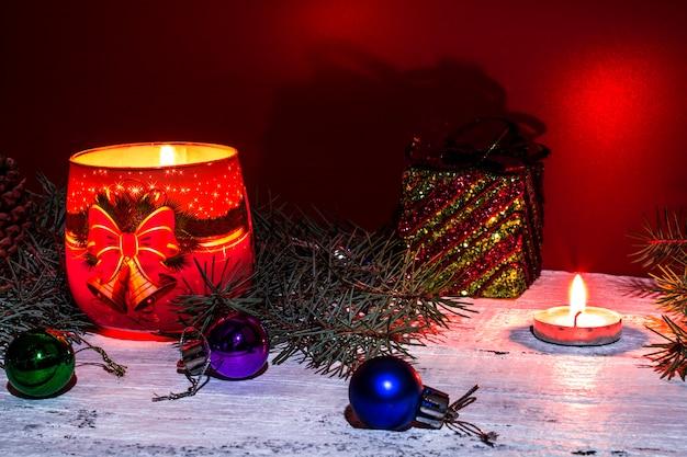 赤と白の背景にモミの枝、燃えるろうそく、ギフト、クリスマスツリーの装飾とクリスマスの構成。