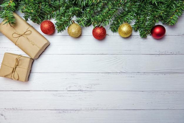 전나무 가지, 금색과 빨간색 풍선 및 흰색 나무 바탕에 공예 종이로 만들어진 선물 크리스마스 구성.