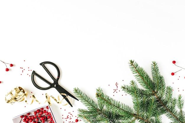モミの枝、赤いベリー、白い表面の装飾が施されたクリスマスの構成。フラットレイ、上面図