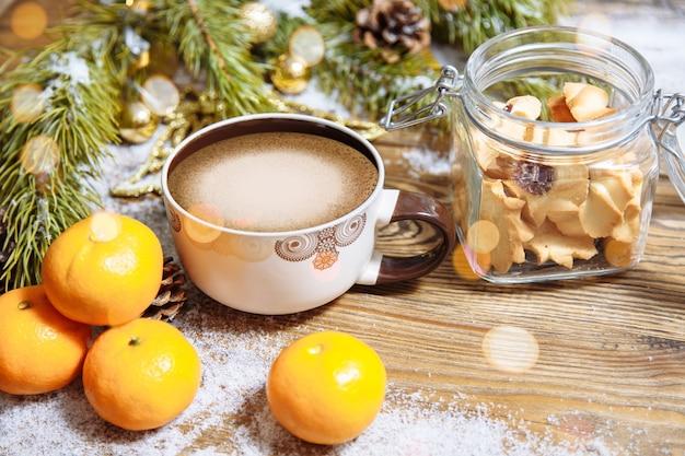 モミの木の枝、クッキー、一杯のコーヒーとみかんのクリスマスの構成
