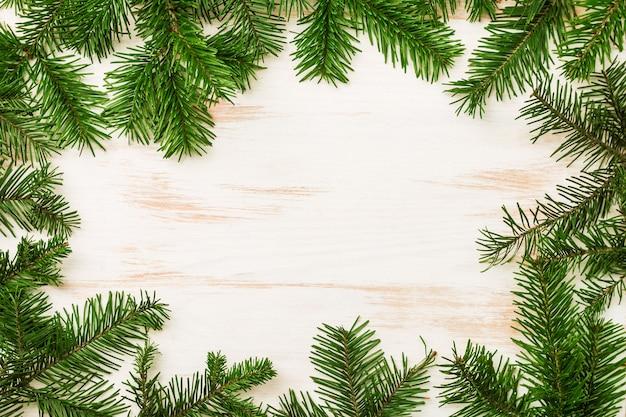 コピースペースと白い木製の背景の上面図にモミの木の枝とクリスマスの装飾とクリスマスの構成