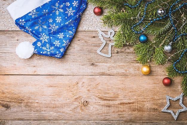コピースペースと木製の背景の上面図にモミの木の枝とクリスマスの装飾とクリスマスの構成