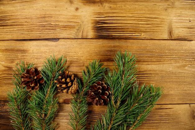 Рождественская композиция с еловыми ветками и шишками на деревянных фоне. вид сверху, копировать пространство