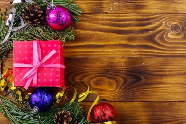 モミの木の枝、ギフトボックス、木製のテーブルの上のクリスマスの装飾とクリスマスの構成。上面図、コピースペース