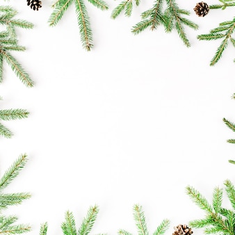 Christmas composition with frame of fir branches and pine cones.