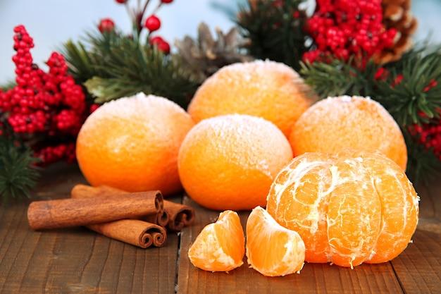 Новогодняя композиция с матовыми спелыми мандаринами на деревянных фоне
