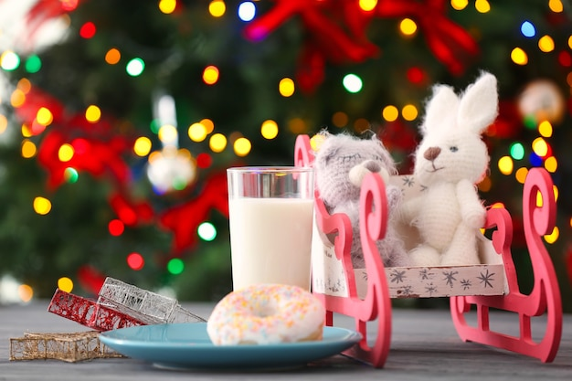 Christmas composition with funny toys, milk and donut on blurred lights tree