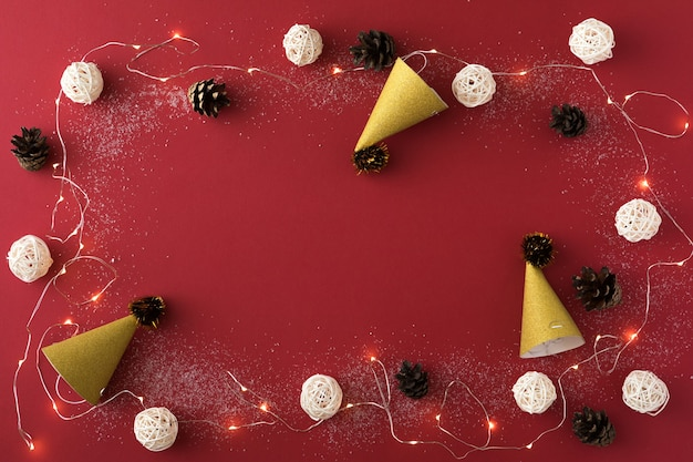 Новогодняя композиция с гирляндой и белыми шарами на красном фоне. плоская планировка рождества, зимы, нового года концепции. вид сверху и копировать пространство