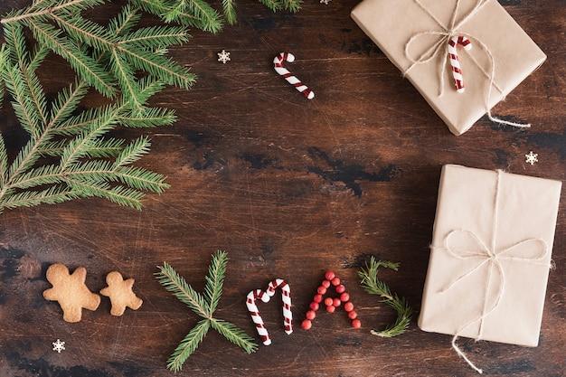 木製の暗い背景にギフトとジンジャーブレッドマンとクリスマスの作曲。クリスマスのクリスマスのテキスト、松ぼっくり、木製の机の上のモミの枝、フラットレイと上面図、コピースペース