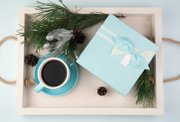 Christmas composition with a gift box, a cup of coffee, christmas balls and a pine branch on a white tray
