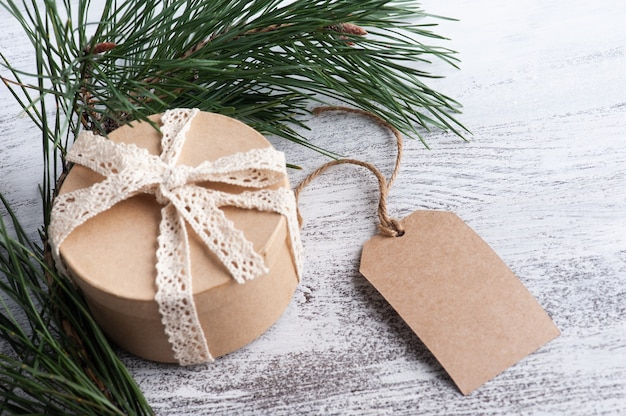 Christmas composition with gift box, kraft tag and pine tree branches, mockup for greeting or advertasing