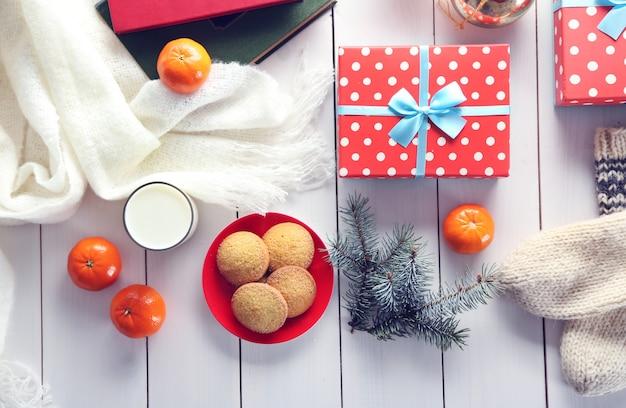 Новогодняя композиция с подарочными коробками, печеньем и украшениями на белом столе