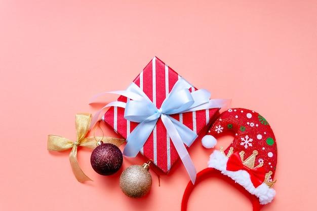Новогодняя композиция с подарочными коробками, шляпой санты и украшениями. плоский вид сверху