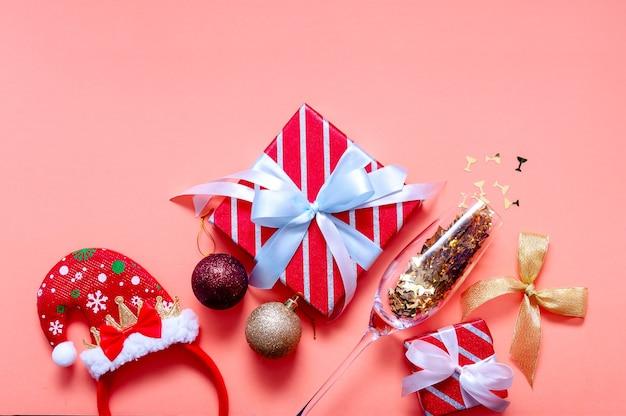 ギフトボックス、サンタ帽子、シャンパングラス、デコレーション付きのクリスマス作曲。上面図フラットレイ