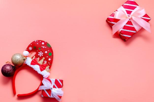 Новогодняя композиция с подарочными коробками, шляпой санты, бокалом шампанского и украшениями. плоский вид сверху