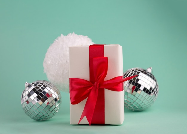 Новогодняя композиция из подарочных коробок с красным бантом, праздничным декором, снежками