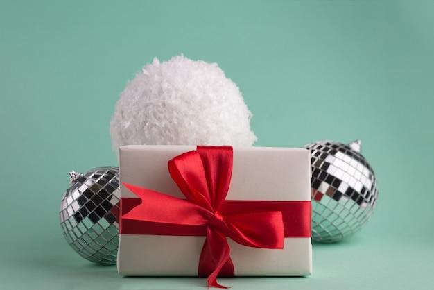 Новогодняя композиция с подарочными коробками с красным бантом, праздничными украшениями, большими снежками