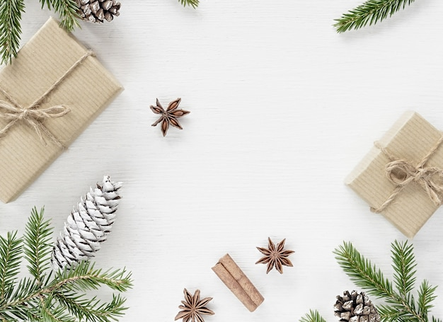 Christmas composition with gift boxes wrapped in kraft paper, fir branches pine cones and christmas spices on white wooden background. copy space, flat lay