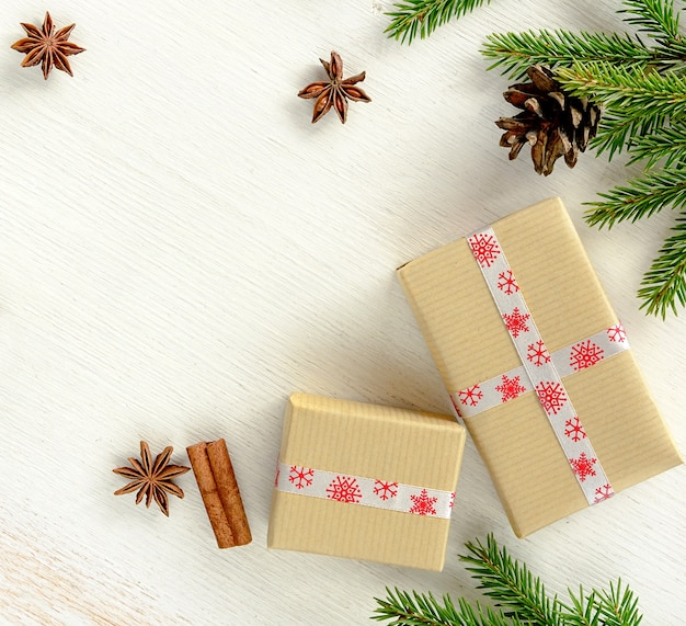 Christmas composition with gift boxes wrapped in kraft paper, fir branches with cone and christmas spices cinnamon stick, anise stars on white wooden background. copy space