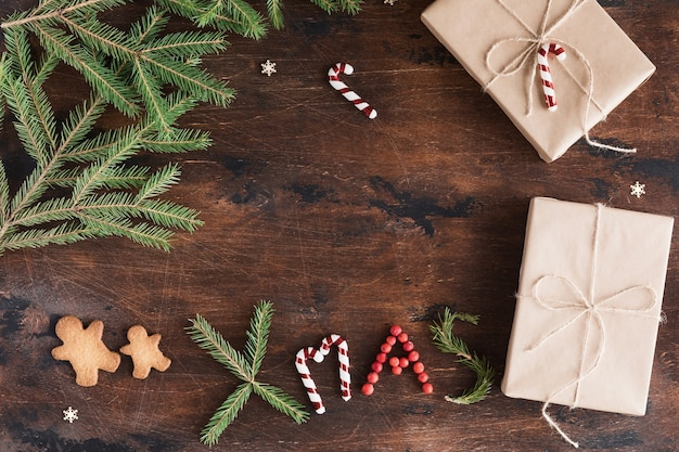 Christmas composition with gift and gingerbread man on wooden dark background. christmas xmas text, pine cones, fir branches on wood desk, flat lay and top view, copy space