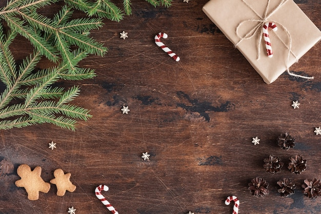 Christmas composition with gift and gingerbread man on wooden dark background with pine cones, fir branches on wood desk, flat lay and top view, copy space