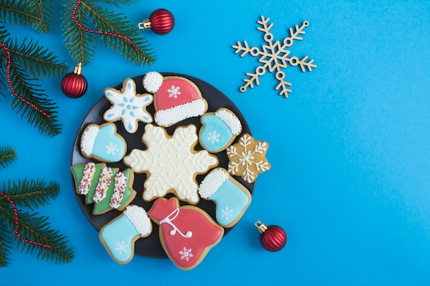 Christmas composition with gingerbread on the black plate on the blue background. top view. copy space.