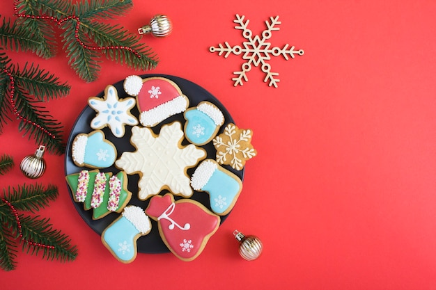 Christmas composition with gingerbread on the black plate on the red background. top view. copy space.