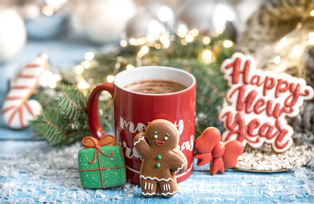 Christmas composition with gingerbread cookies and red cup of hot drink