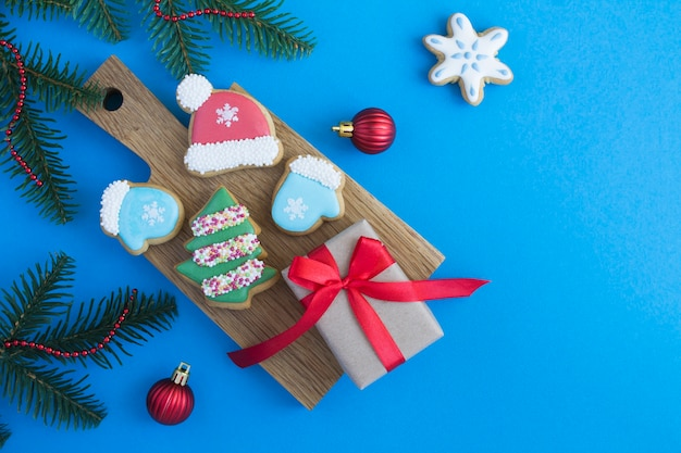 Christmas composition with gingerbread and gift box on the wooden cutting board  on the blue background. top view. copy space.