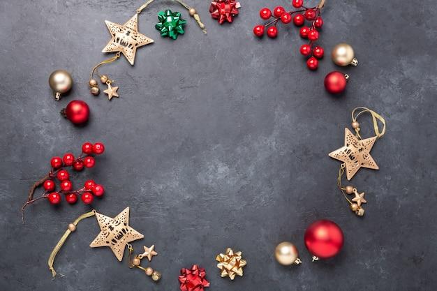 어두운 돌 배경에 금색과 빨간색 장식이 있는 크리스마스 구성. 상위 뷰 복사 공간 - 이미지