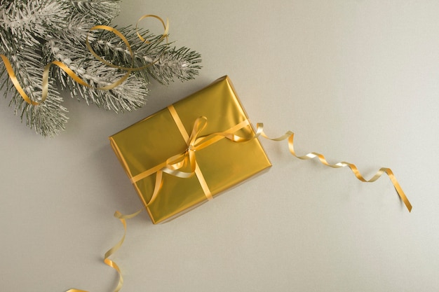 Christmas composition with gold gift box on the gray background. top view. copy space.