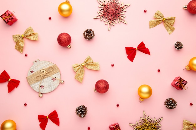 Christmas composition with gold and red decoration on pink