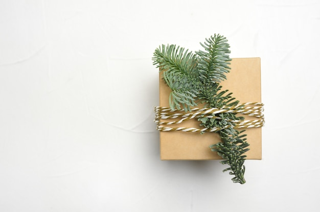 Christmas composition with green fir branches and kraft gift box on white wooden background with copyspace.