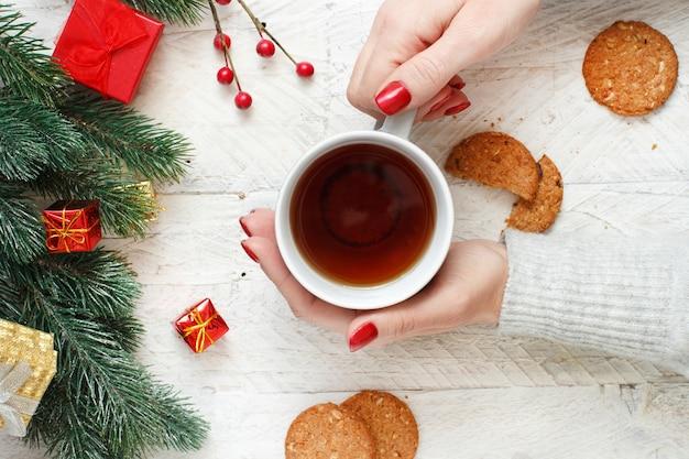 Рождественская композиция с руками, держащими кружку чая и печенье на столе